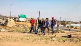 Giovani uomini africani che camminano a Soweto urbana Sudafrica Fotografie Stock Libere da Diritti