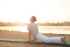 Giovani uomini atletici che fanno yoga sulla sabbia nel parco Immagini Stock
