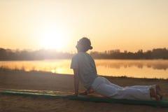 Giovani uomini atletici che fanno yoga sulla sabbia nel parco Fotografia Stock Libera da Diritti