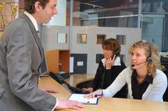 Giovani uomini di affari che firmano dentro Immagini Stock