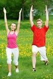 Giovane e donna che fanno allungando gli esercizi Immagini Stock Libere da Diritti