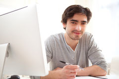 Giovani uomini rilassati che scrivono all'ufficio Immagine Stock
