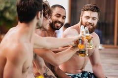 Giovani uomini sorridenti bei divertendosi nella piscina immagini stock
