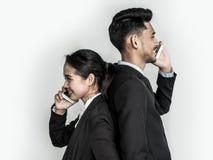 Giovani uomo e donna di affari con la conversazione sullo smartphone isolato su fondo bianco fotografia stock