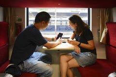 Giovani uomo e donna turistici che usando sul telefono sul treno mentre viaggio fotografia stock libera da diritti