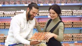 Giovani uova di acquisto della famiglia alla drogheria Movimento lento Ritratto stock footage
