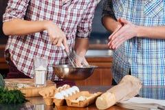 Giovani uova di battitura delle coppie ed omelette di cottura sulla cucina Immagini Stock