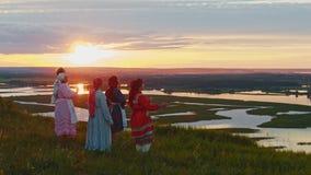 Giovani in vestiti tradizionali russi che stanno sul campo e che godono della vista sul tramonto - fiume e poco archivi video