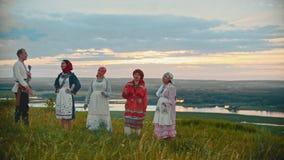 Giovani in vestiti tradizionali russi che stanno sul campo su un fondo del fiume e delle isole stock footage