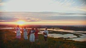 Giovani in vestiti tradizionali russi che stanno sul campo su un fondo di bello tramonto e che cantano archivi video