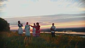 Giovani in vestiti tradizionali russi divertendosi sul campo su un fondo di bello tramonto - un gioco dell'uomo archivi video