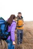 Giovani viaggiatori con zaino e sacco a pelo che stanno nell'erba asciutta Fotografia Stock Libera da Diritti