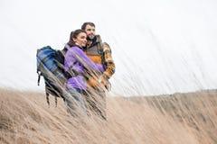 Giovani viaggiatori con zaino e sacco a pelo che stanno nell'erba asciutta Fotografia Stock