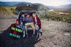 Giovani viaggiatori degli amici che si siedono sul tronco dell'automobile e che esaminano la mappa di carta Turisti felici dei pa immagini stock