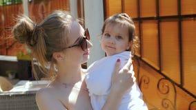 Giovani wips della mamma la sua piccola figlia dopo il nuoto nello stagno di aria aperta stock footage