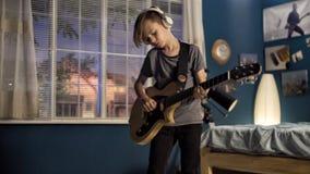 Giovanotto con la chitarra in camera da letto fotografia stock libera da diritti