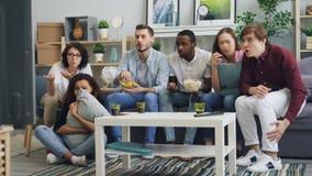 Gioventù che guarda le notizie tragiche sulla TV a casa che esprime timore negativo di emozioni stock footage