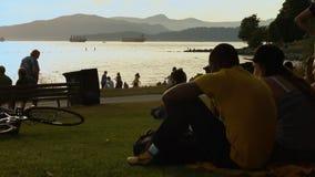 Gioventù della spiaggia che chiacchierano con le navi nel fondo stock footage