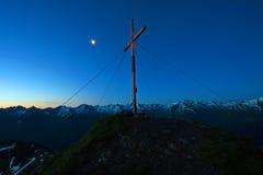 Gipfelkreuz am Morgen Stockbilder