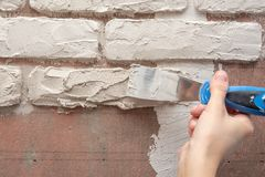 Gipser arbeitet manuell mit einer Spachtel und macht den Gips auf der Wand glatt lizenzfreie stockfotos