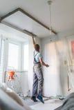 Gipser, der Innenwände und Decken erneuert Fertigungsarbeiten stockfotografie