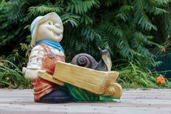 Gipsfigur des Gärtners mit einer Schnecke Stockfoto