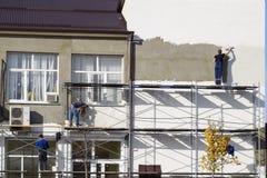 Gipsiarzów budowniczowie gipsowali ścianę w handlowym budynku Wor obraz royalty free