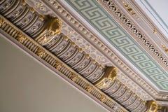 Gipspleister en luxueuze decoratieve elementen op plafond Luxe esthetisch in een huisdecor Gouden leeuw hoofdstukken op een plafo stock afbeeldingen