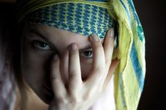Gipsy girl. Looking through her fingers, on black background stock photo