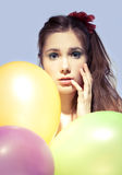 Gir with balloons. Beautiful girl hiding in colorful balloons, blue background Stock Photography