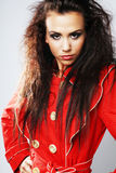 Gir with curly long hair in red coat. Stock Image