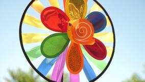 Gir?ndola do brinquedo multi-colorido, girado pelo vento contra um c?u azul decora??es coloridas para um partido das crian?as Con filme