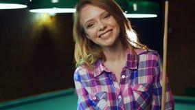 Gir rubio atractivo que se sienta con señal en la sonrisa del ANG de la tabla almacen de video