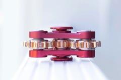 girador vermelho do brinquedo sob a forma de um mecanismo com as engrenagens, colocando sobre Imagem de Stock