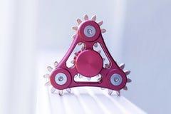 Girador vermelho do brinquedo sob a forma de um mecanismo com engrenagens Fotografia de Stock Royalty Free