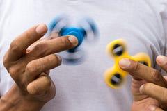 Giradores azuis e amarelos ambos nas mãos imagens de stock