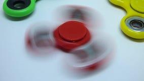 Giradores brilhantes do amarelo, os verdes e os vermelhos da inquietação do dedo no fundo branco filme