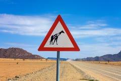 Girafas que cruzam o sinal de estrada de advert?ncia colocado no deserto de Nam?bia imagem de stock