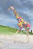 Giraffa colorata che viene a voi sul fondo profondo del cielo blu Fotografia Stock