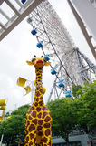 Giraffe παιχνιδιών κάτω από τη ρόδα Ferris στοκ φωτογραφία με δικαίωμα ελεύθερης χρήσης