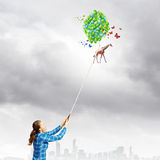 Giraffe on lead. Young woman in casual and giraffe flying in sky Royalty Free Stock Photo