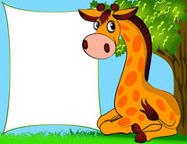 Giraffe sitting beside papers and tree Royalty Free Stock Photography