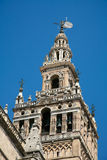 Giralda belfry in Seville cathedral. Famous belfry named Giralda and vane Giraldillo, in landmark catholic cathedral of Saint Mary of the See, public gothic stock photo