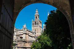 The Giralda in Seville through an arch. View of the Giralda, the bell tower of the Cathedral of Seville in Spain, through an ancient stone arch. Originally the Stock Photos