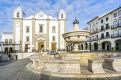 Giraldo Square with fountain and Saint Anton`s church, Evora, Al. Low-angle shot of a fountain and Saint Anton`s Church, Giraldo Square, Evora, Alentejo Royalty Free Stock Photography
