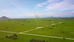 Girando lentamente a fileira das turbinas eólicas no vale verde vídeos de arquivo