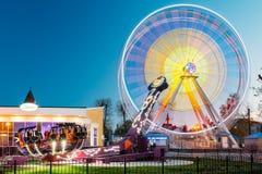 Girando nell'attrazione illuminata effetto Ferris Wheel On Summer Evening di moto nel parco di divertimenti della città Fotografia Stock Libera da Diritti
