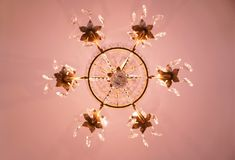 Optical illusion hexagonal chandelier. Girandole suspended light fixture illuminating the ceiling with warm pink glow with clear crystal ornamental prisms as royalty free stock photo
