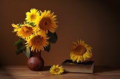Girasol en un florero de cerámica, libros y una cesta de mimbre Fotografía de archivo