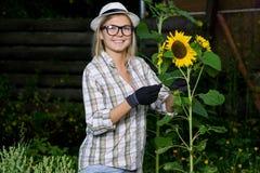 Girasole seguente stante sorridente dell'agricoltore della giovane donna in villaggio Fotografia Stock
